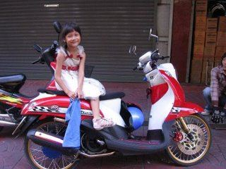 Girl on motorbike, Chinatown, Bangkok, Thailand
